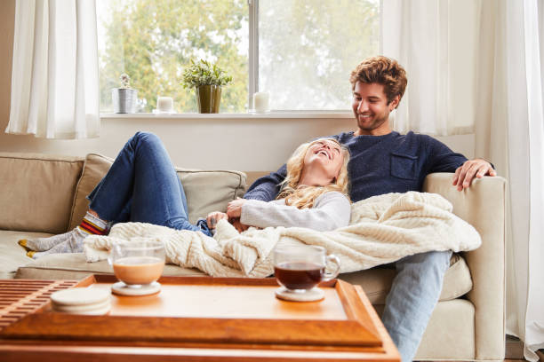 Young couple talking while relaxing on their living room sofa stock photo