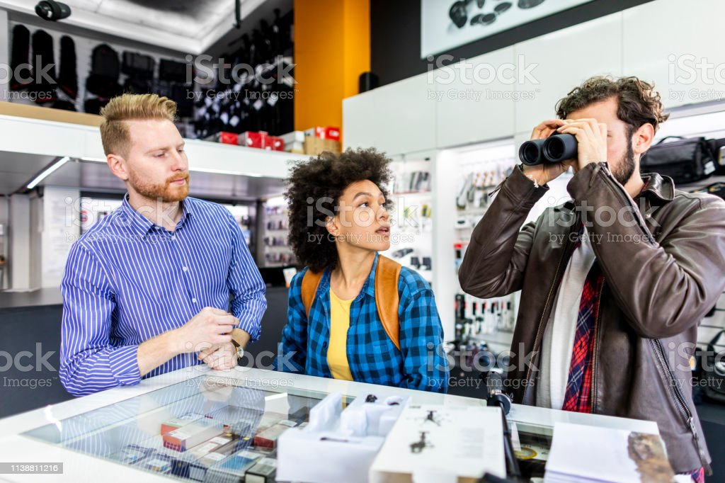 Young couple checking out some binoculars in a camera shop with a...