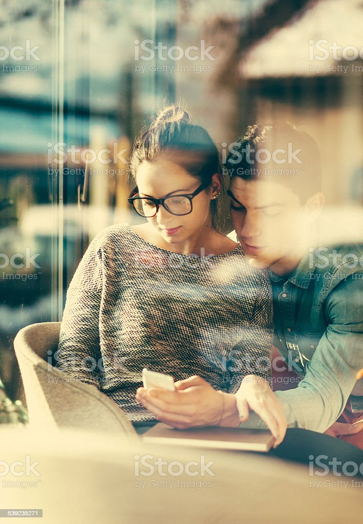 Young couple text messaging at the coffee shop royalty-free stock photo