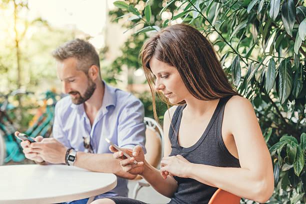 young couple texting and surfing the net - kvinna cloes up bildbanksfoton och bilder