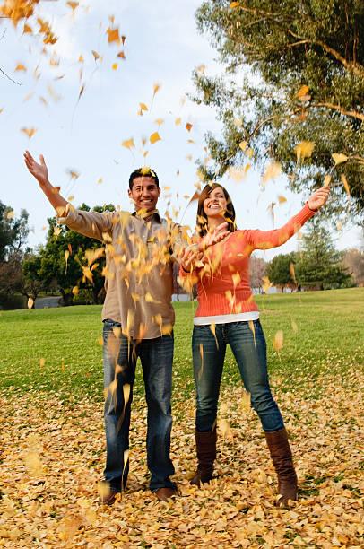 junges paar wurf blätter in die luft im park - mark tantrum stock-fotos und bilder