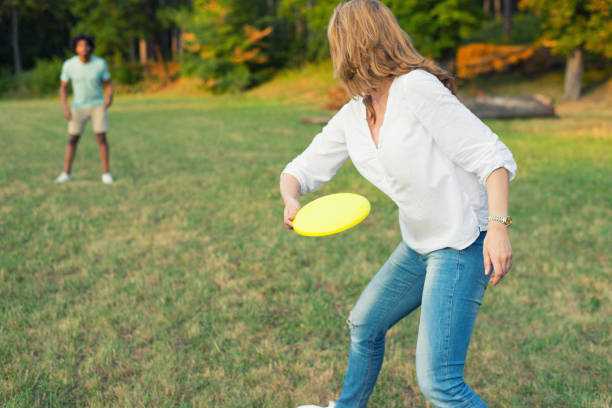Young couple throwing disc in the nature Young couple throwing disc in the nature on a sunny summer day. plastic disc stock pictures, royalty-free photos & images