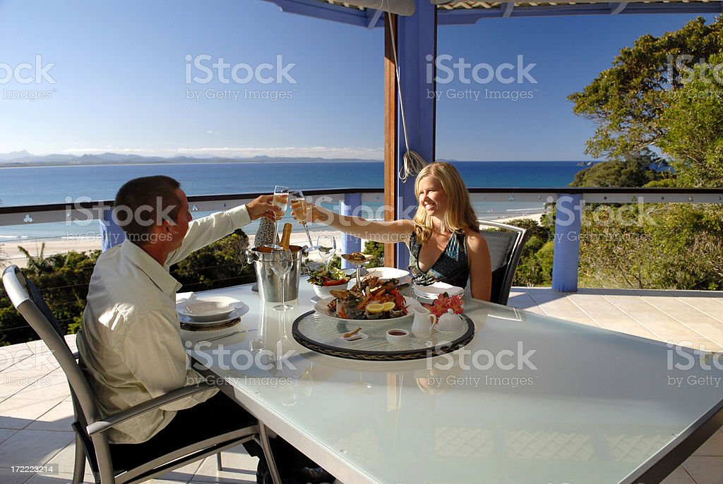 Young couple toasting at dinner in restaurant outside by sea stock photo