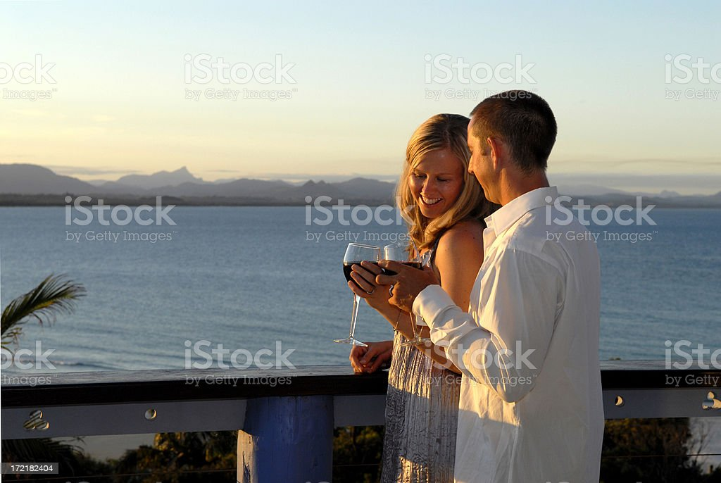 Young couple toasting at sunset on balcony by the sea royalty-free stock photo