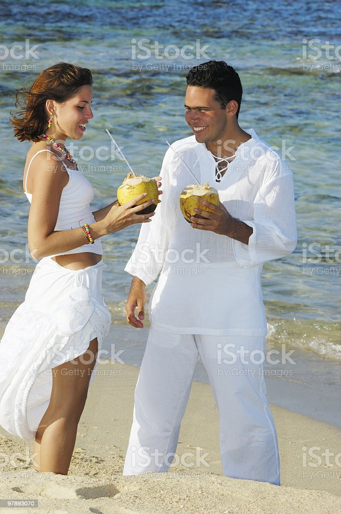 Young couple toasting with coconuts in a tropical beach royalty-free stock photo