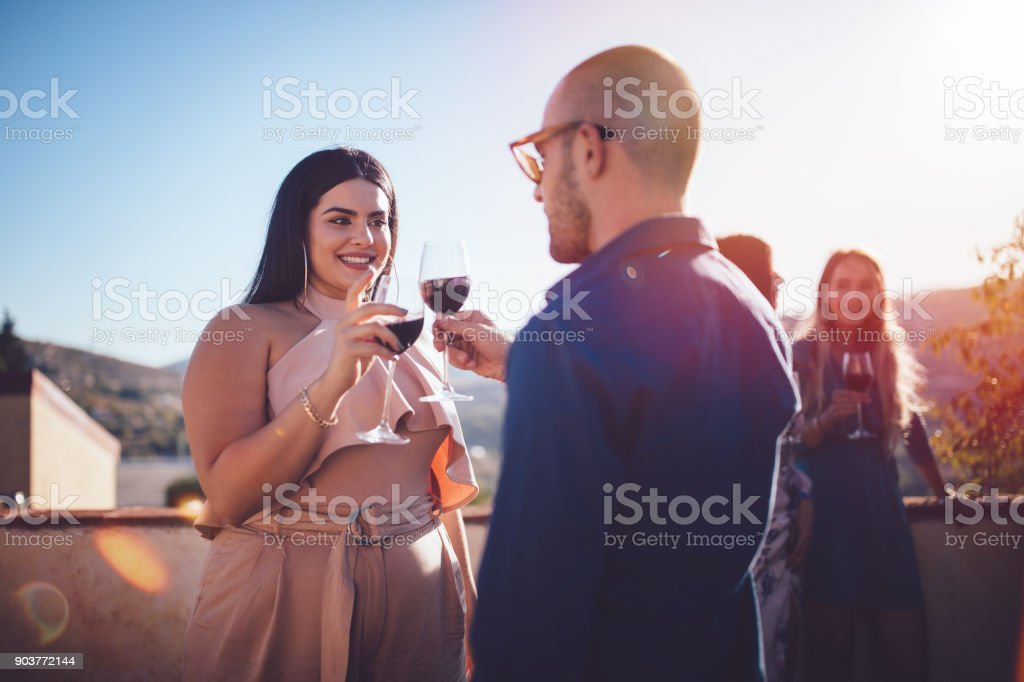 Young couple toasting with red wine at rustic cottage patio stock photo