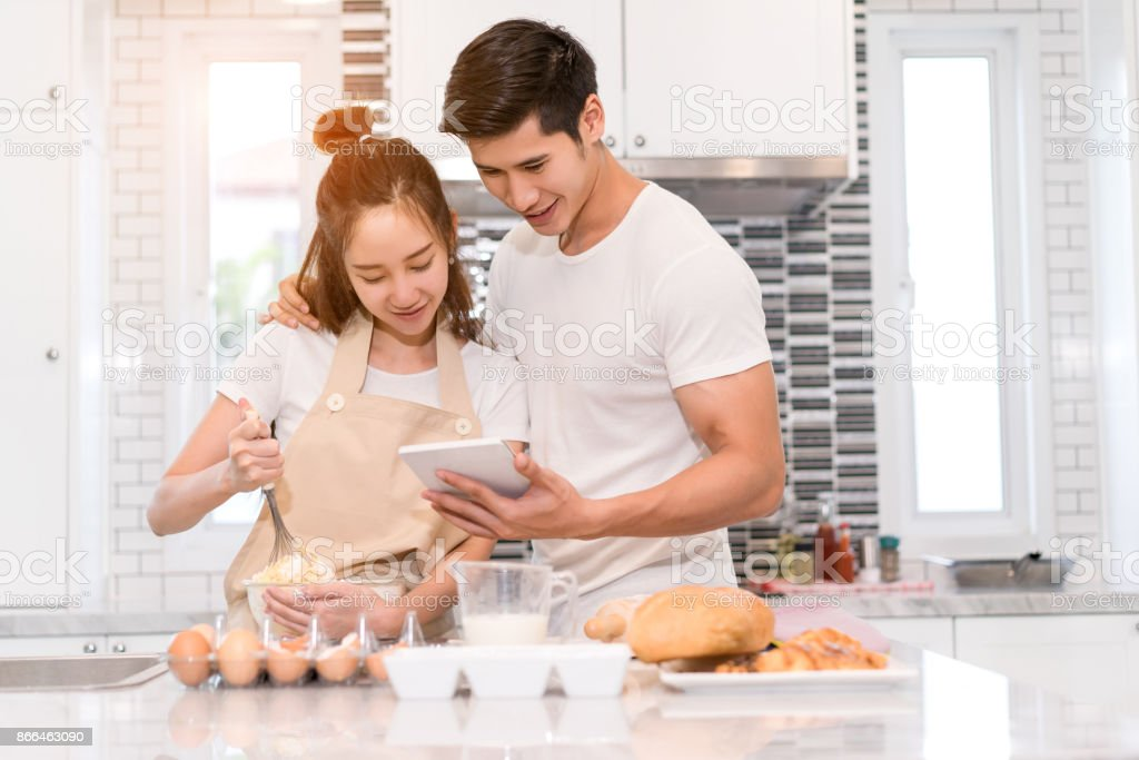 Young Couple Together Cooking Woman First Crack An Egg And Put In