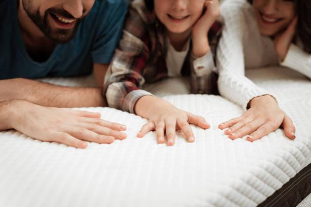 jeune couple avec leur jeune fils test matériel du matelas pour une touche. - matelas photos et images de collection