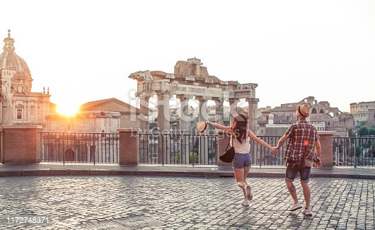 Young couple tourist walking pointing towards Roman Forum at sunrise. Historical imperial Foro Romano in Rome, Italy from panoramic point of view.