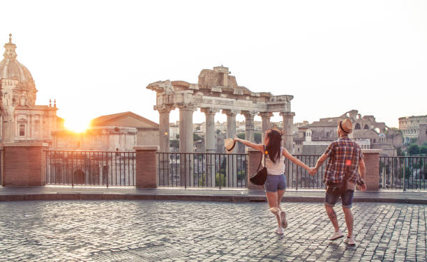 Young couple tourist walking pointing towards Roman Forum at sunrise. Historical imperial Foro Romano in Rome, Italy from panoramic point of view. Young couple tourist walking pointing towards Roman Forum at sunrise. Historical imperial Foro Romano in Rome, Italy from panoramic point of view. rome italy stock pictures, royalty-free photos & images
