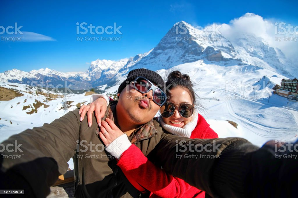 Young Couple Tourists selfie with mobile phone near Kleine Scheidegg station, along the railway from Interlaken to Jungfraujoch (3,466 m). In daylight atI Switzerland stock photo