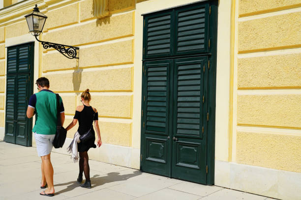 Young couple tourists walking past yellow stone wall with two green doors under street lamp. stock photo