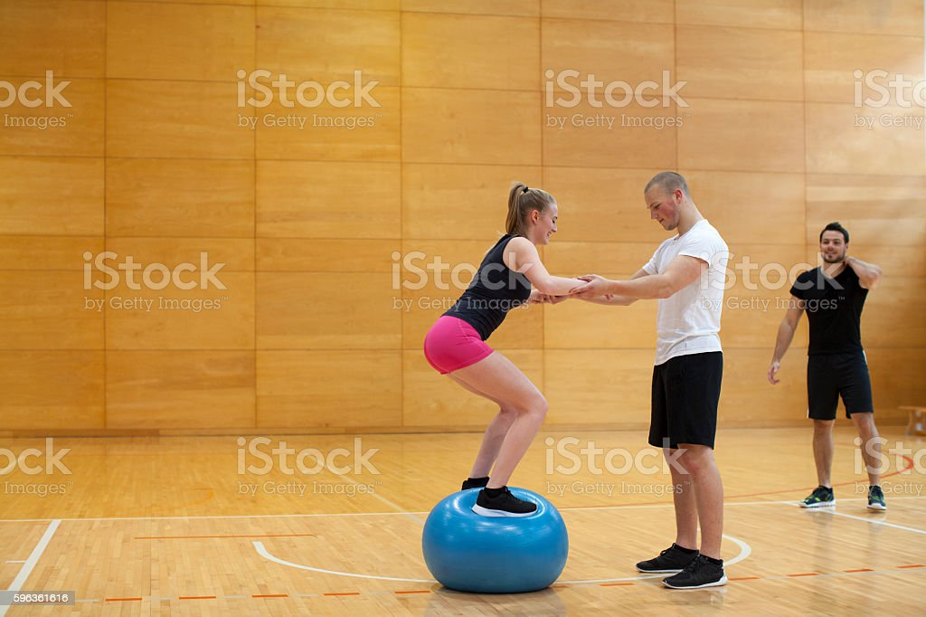 Young Couple Training with Instructor Indoor Gym royalty-free stock photo