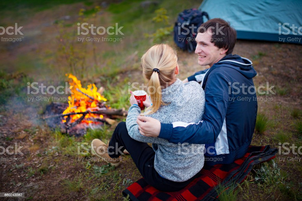Young couple traveler sitting by the fire and drinking tea stock photo