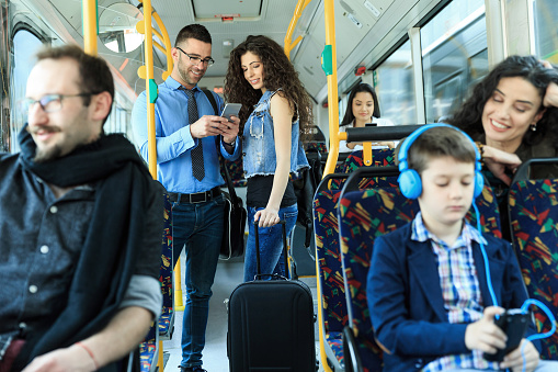 Smiling young couple traveling in bus and using smart phone. Both with casual clothes.