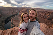 Couple traveling in USA take selfie picture at the horseshoe bend; people adventure travel concept