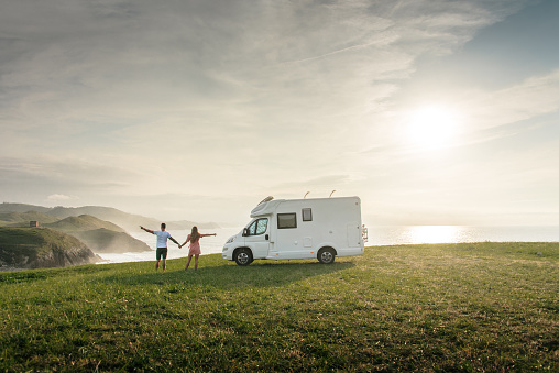 Young couple traveling with their motor home standing by the sea with arms raised