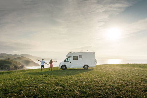 Young couple traveling with their motor home standing by the sea with arms raised stock photo