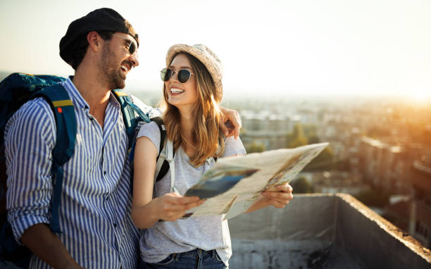 young couple travelling with a map in the city - travel imagens e fotografias de stock