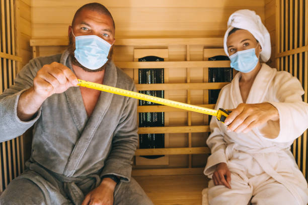 Young couple trying to relax in SPA during corona virus pandemic, using medical face masks and measuring social distance in a small infrared sauna