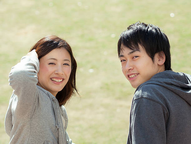 Young couple turning around A couple turns around with a smile. only japanese stock pictures, royalty-free photos & images