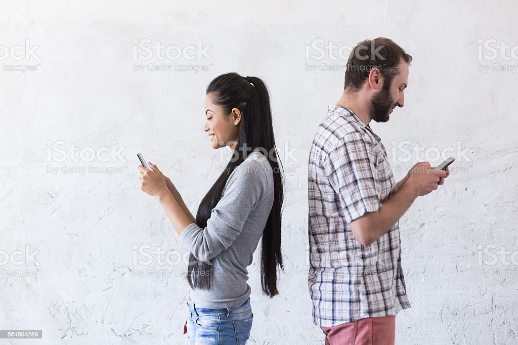 Young couple typing messages on smart phone at new home stock photo