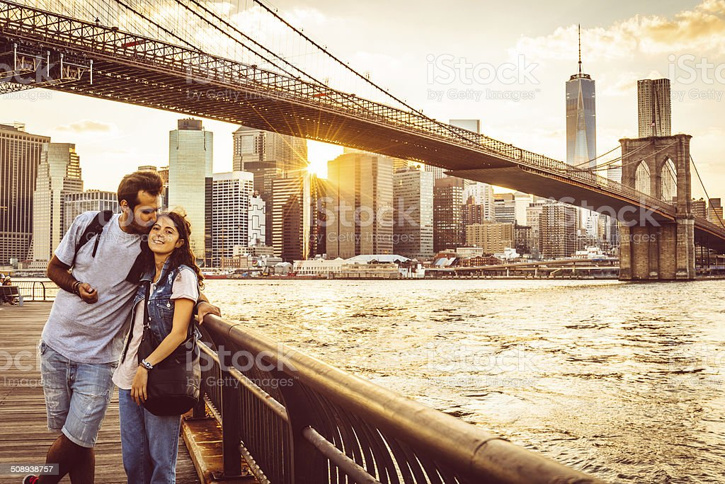 Young Couple Under Brooklyn Bridge at sunset stock photo