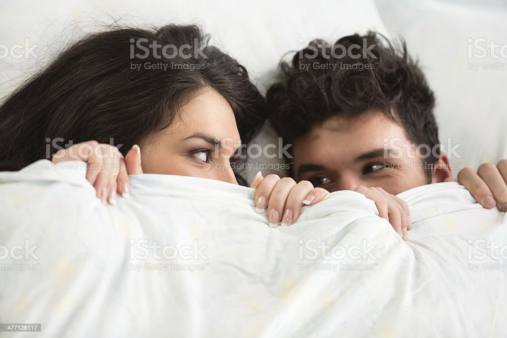 Young couple under covers in bed stock photo