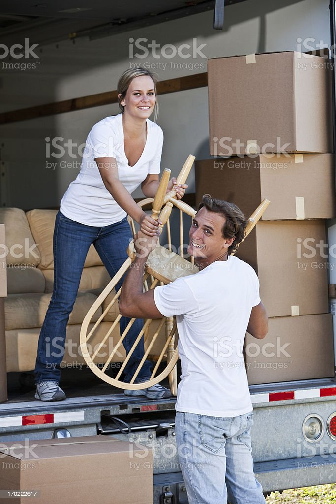 Couple moving house, loading or unloading chairs from back of moving...