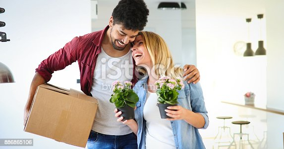 istock Young couple unpacking cardboard boxes at new home moving in concept 886865106