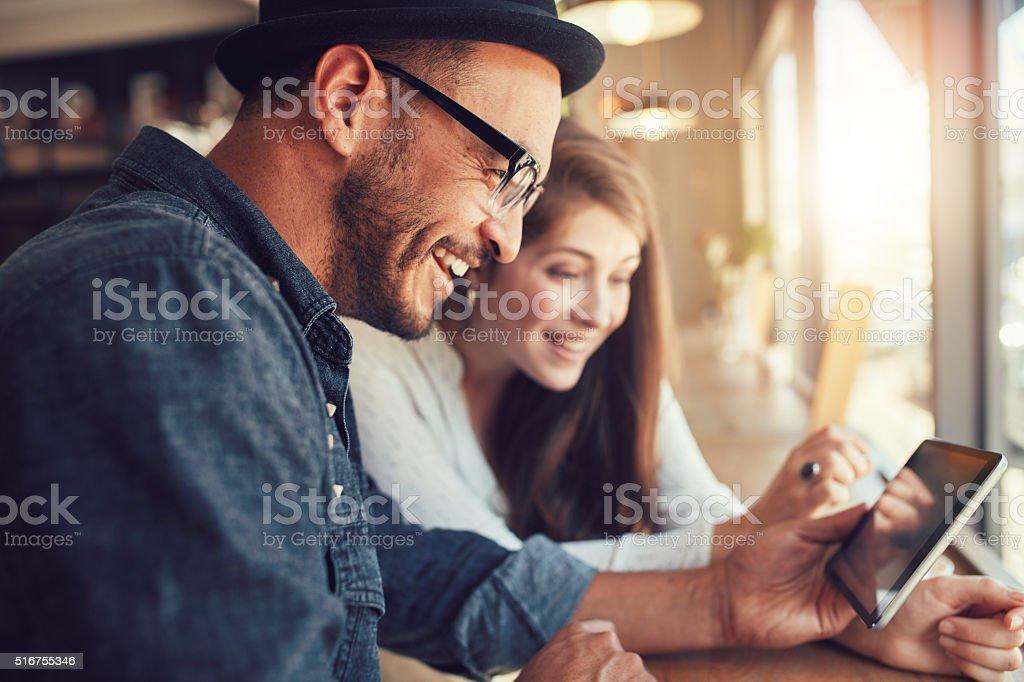 Junges Paar mit einem Digitaltablett in einem Kaffee Shop Lizenzfreies stock-foto