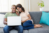 Young couple using a laptop while relaxing on a sofa in the living room