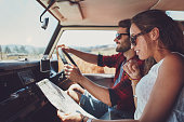 Side view of young couple using a map on a roadtrip for directions. Young man and woman reading a map while sitting in a car.