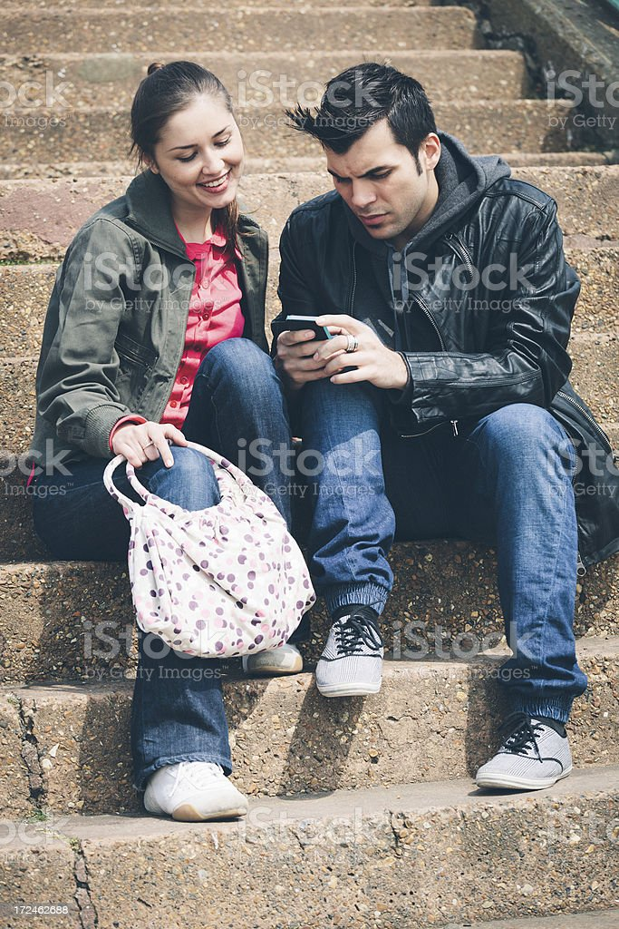 Young couple using a smartphone royalty-free stock photo