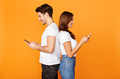 Problem of modern relationships. Young couple using cellphones and browsing information standing back to back