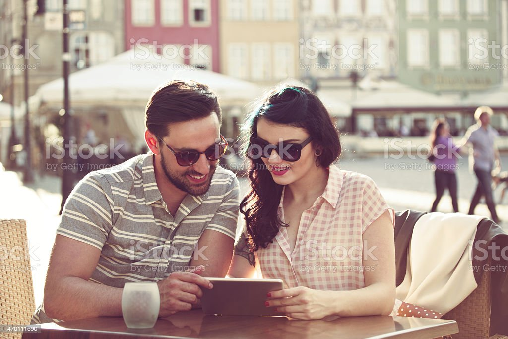 Young couple using digital tablet in the outdoor restaurant Happy young couple wearing sunglasses sitting at the table in outdoor restaurant in the city and using a digital tablet together. Summer time.  2015 Stock Photo