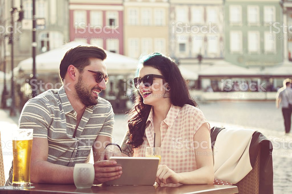 Young couple using digital tablet in the outdoor restaurant Happy young couple wearing sunglasses sitting at the table in outdoor restaurant in the city, using a digital tablet together and having fun. Beer on the table. Summer time.  2015 Stock Photo