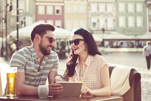 Young Couple Using Digital Tablet In The Outdoor Restaurant Stock Photo - Download Image Now