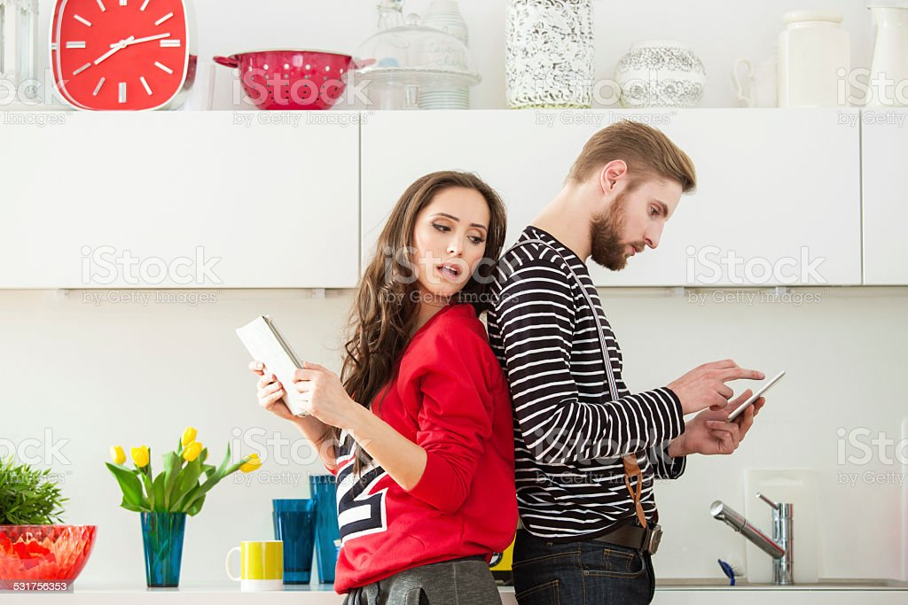 Young couple using digital tablets at home stock photo
