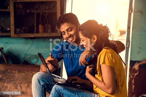 Young Indian Couple Using Laptop in a farmhouse near mysore
