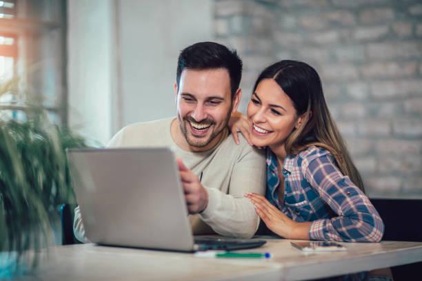pareja joven con laptop en el escritorio en casa - online shopping fotografías e imágenes de stock