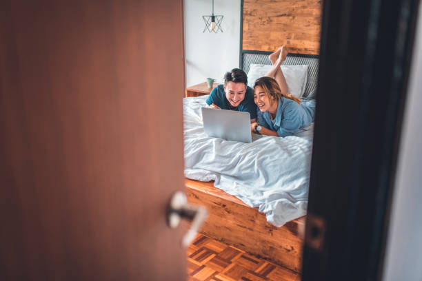 Junges Paar mit laptop beim liegen auf dem Bett – Foto