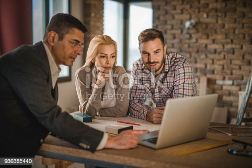 istock Young couple using laptop with building contractor at construction site. 936385440