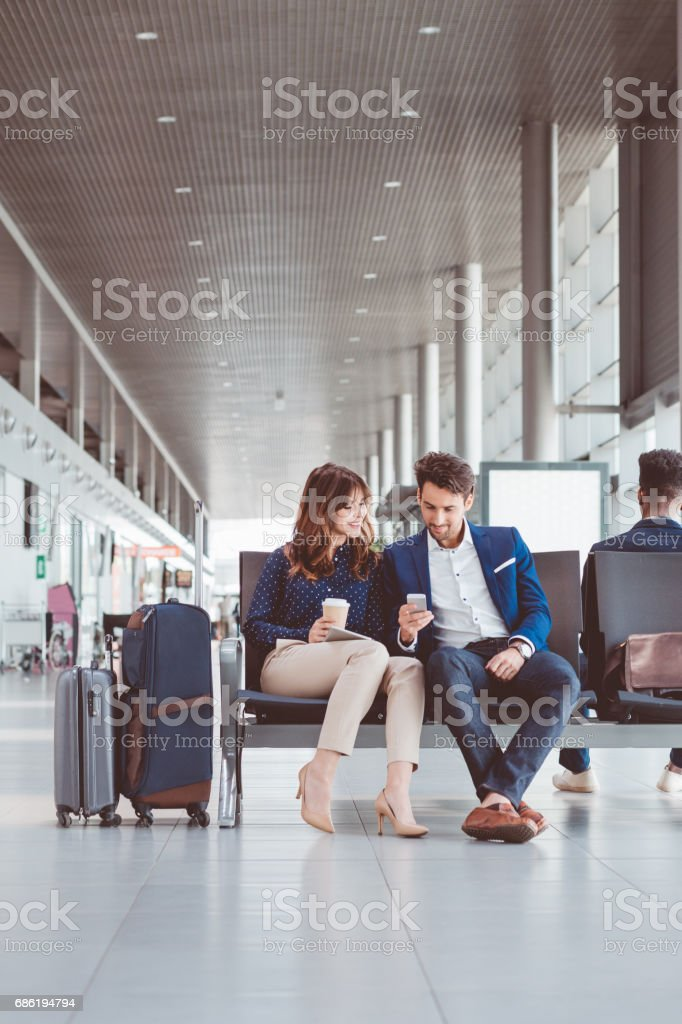 Young couple using mobile phone at the airport stock photo