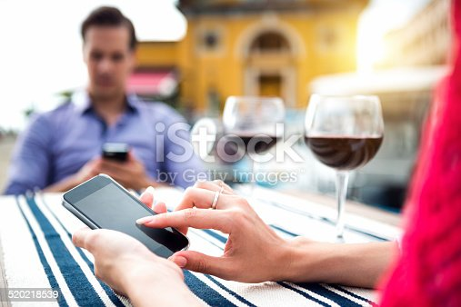 istock Young Couple Using Mobile Phone During Dinner 520218539