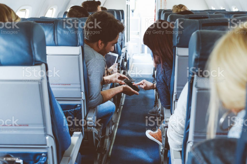 Young couple using mobile phone in the flight stock photo