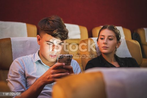 istock Young couple using phone in theatre/theater cinema while watching movie 1181201707
