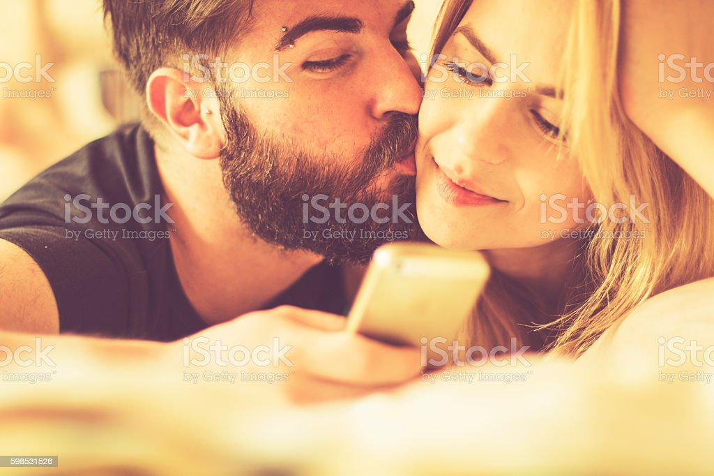 Young couple using smart phone in a bed photo libre de droits