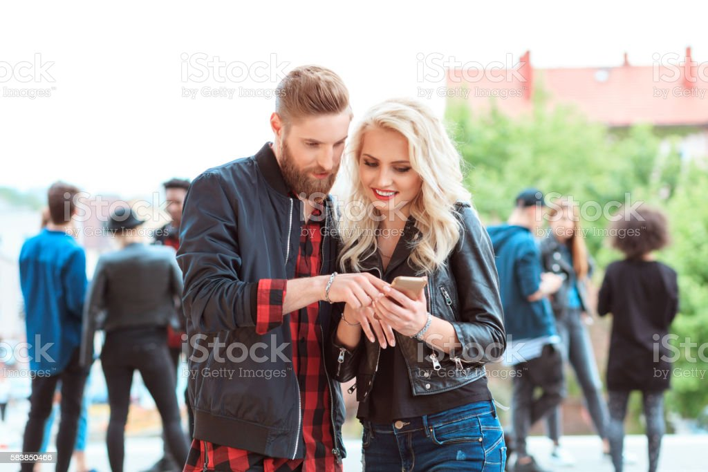 Young couple using smart phone outdoor Hipster young couple using smart phone outdoor. Group of young people in the background. 20-29 Years Stock Photo