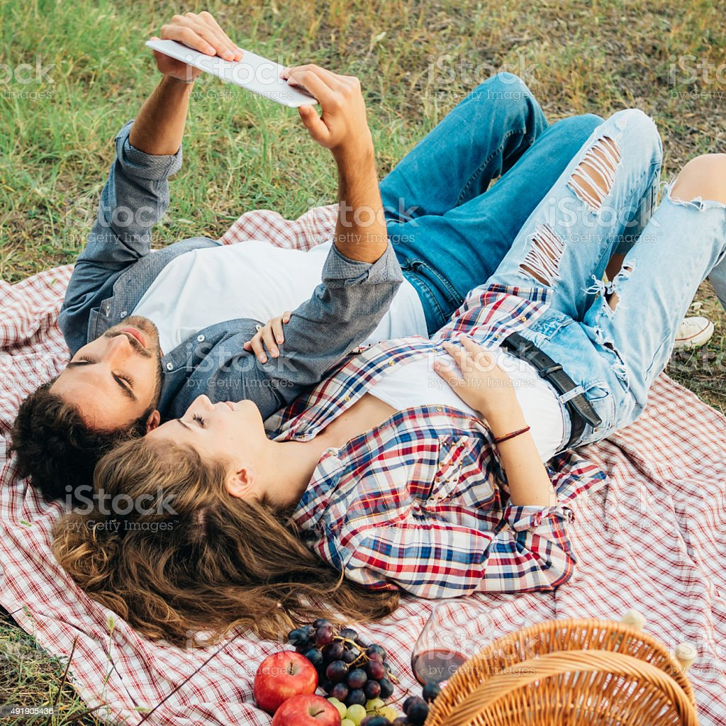 Junges Paar mit Tablet beim Picknick im Freien Lizenzfreies stock-foto